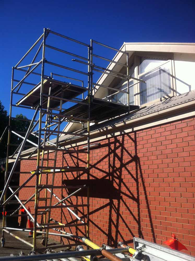 scaffolding by red brick house