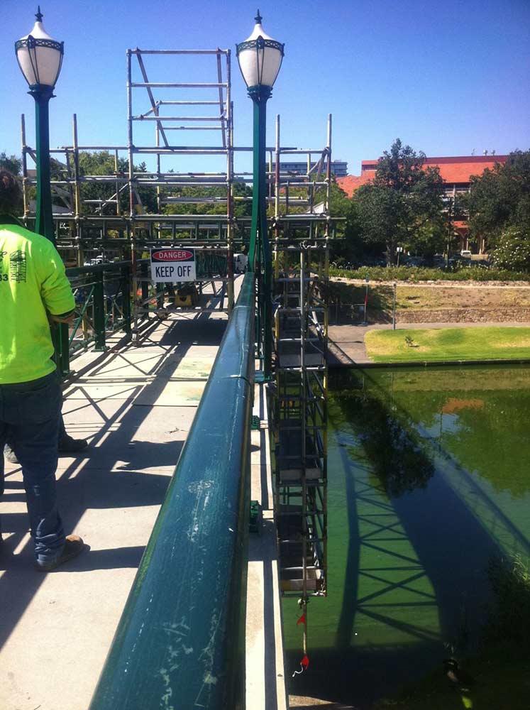 man looking at scaffolding on bridge