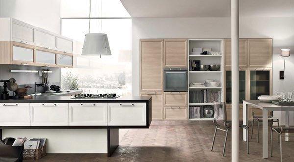 una cucina ad angolo con fornelli a gas e lampade a sospensione