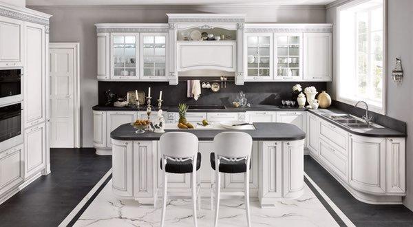 una cucina ad angolo di color bianco in legno con una penisola