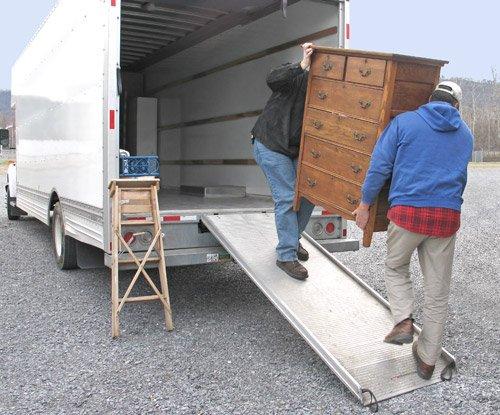 due persone trasportano un mobile dentro un camion