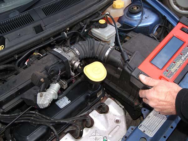 un motore di una macchina e una mano che fa diagnosi computerizzata