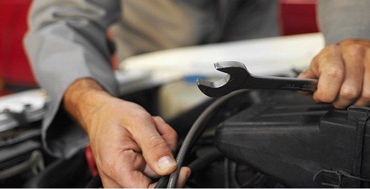 un meccanico con una chiave inglese e un tubo in mano