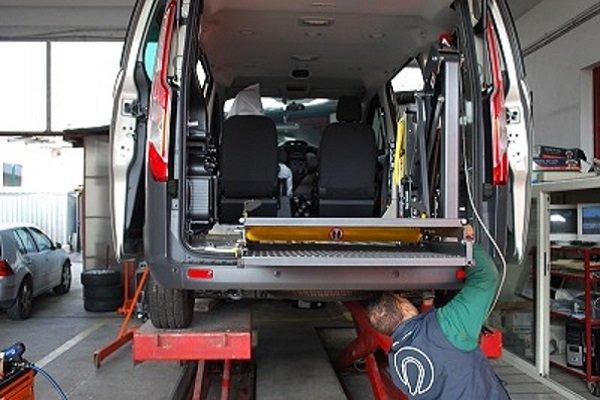 un meccanico che controlla il sotto di un furgone