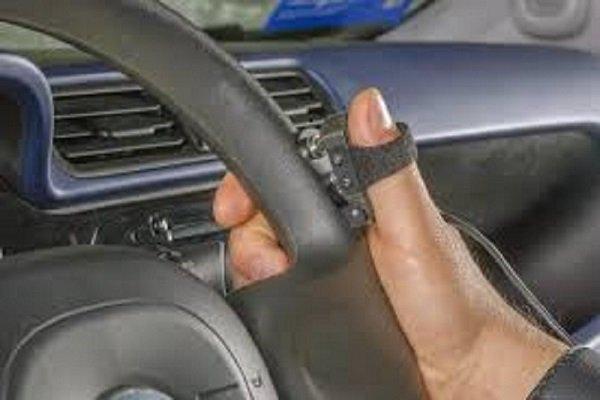 una mano sul volante e sensori sul dito