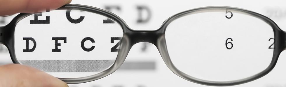 Usando il vetro degli occhiali per vedere chiaro e leggere