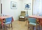 sala con poltrona in un angolo e tavoli
