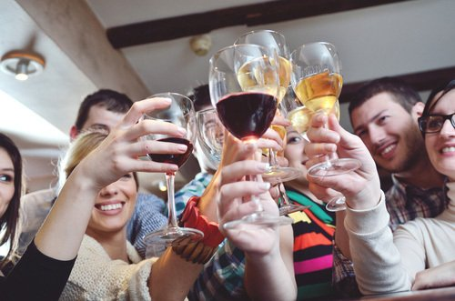 Group of people cheering with wining glasses