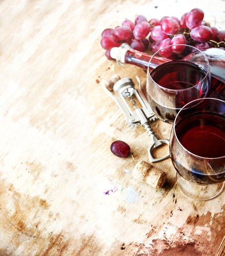 Red wine in glasses, red grapes, on table cork remover