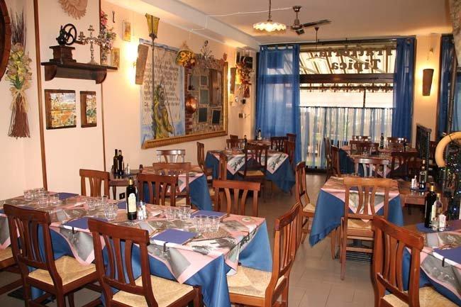 sala interna di un ristorante con tavoli apparecchiati