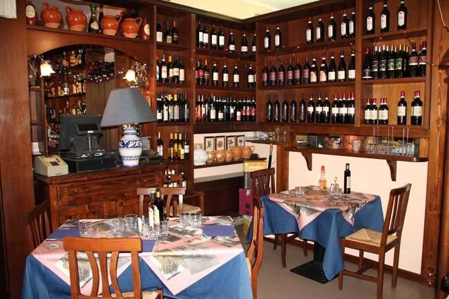 due tavoli in un ristorante e scaffali con vini