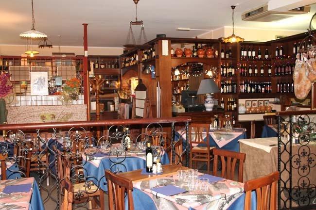 tavoli apparecchiati in un risotrante e muri con scaffali dove bottiglie di viino sono esposte