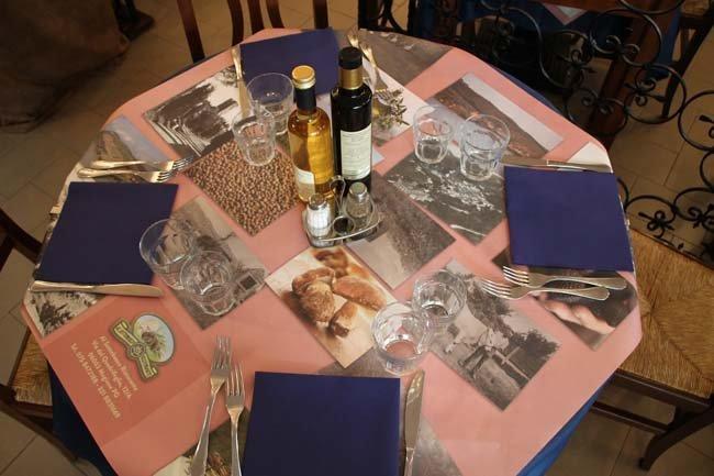tavolo apparecchiati con tovaglioli blu pane olio e vino