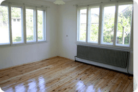 Inside view of modern looking room with wooden flooring and open windows