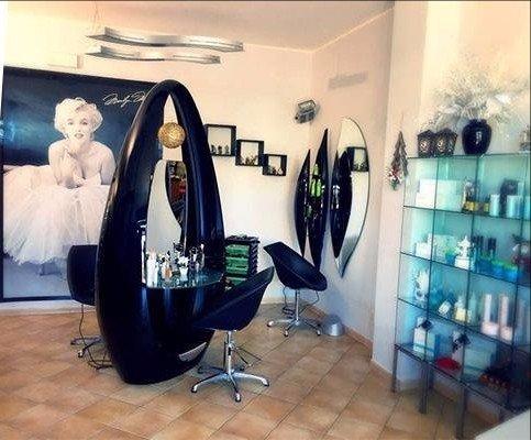 una vetrina con dei prodotti e accanto delle sedie nere in un parrucchiere