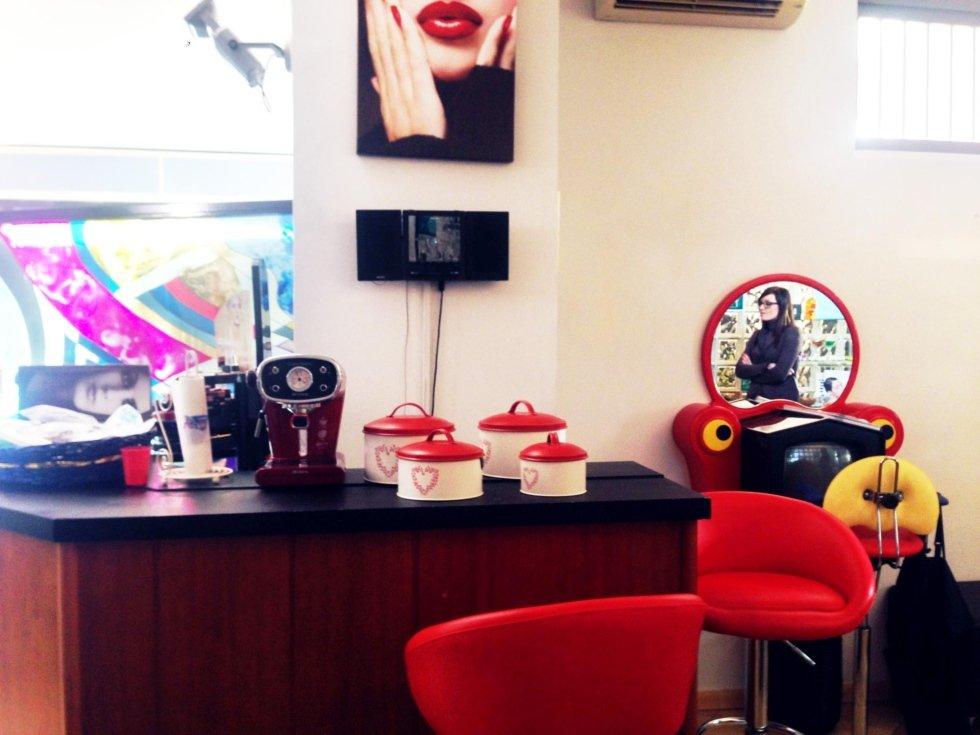 un bancone con una macchina del caffè e degli sgabelli di color rosso