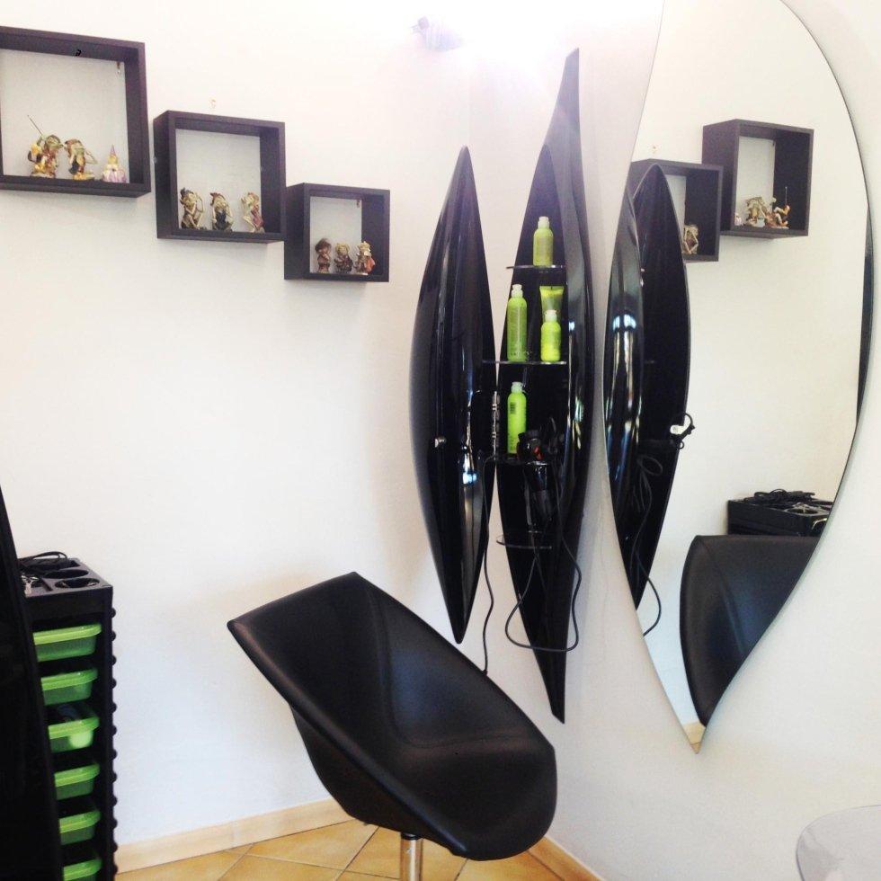 delle mensole di color  nero a muro e uno specchio