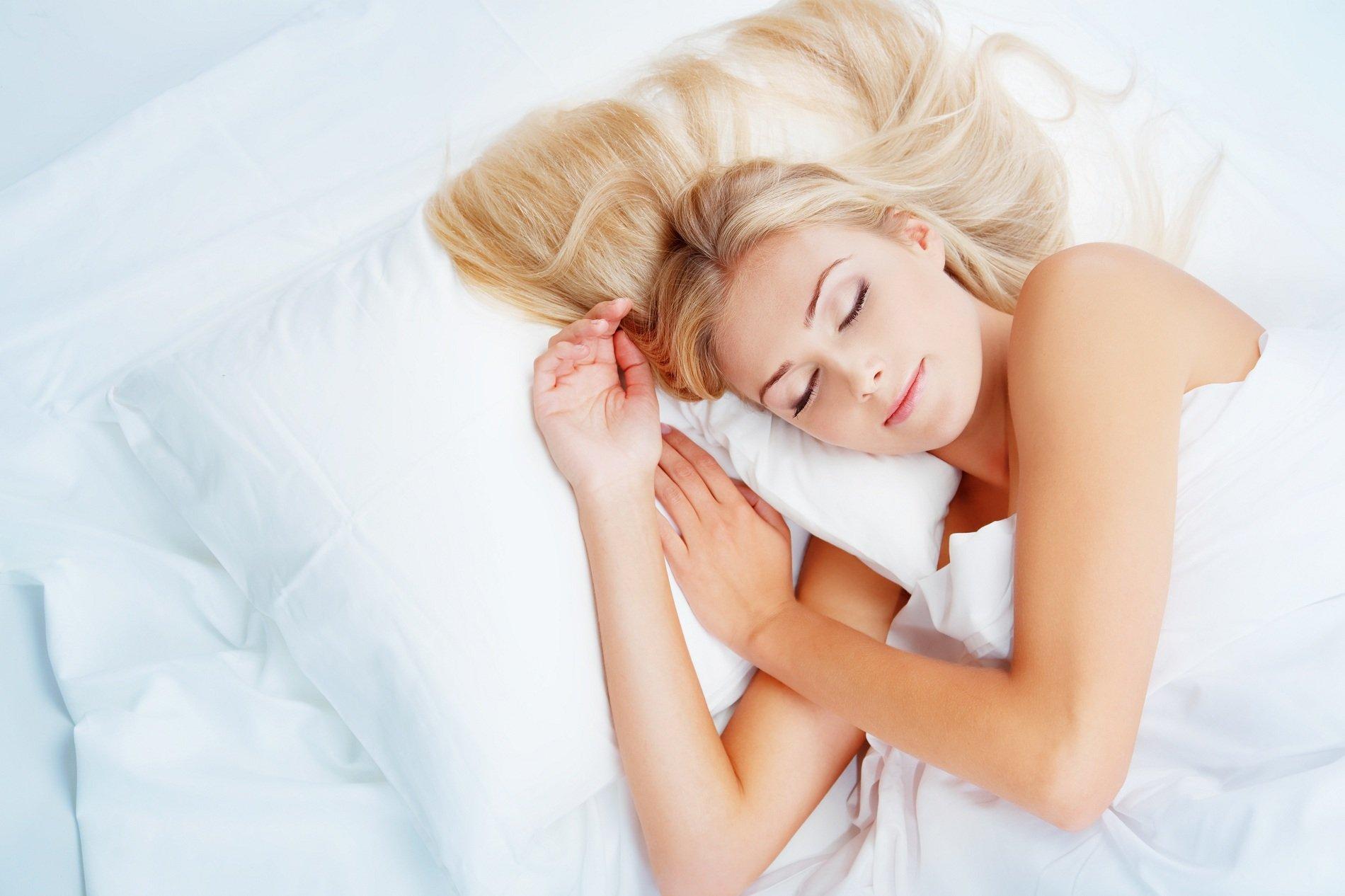 Giovane donna dormendo in un letto con savane bianche e due guanciali