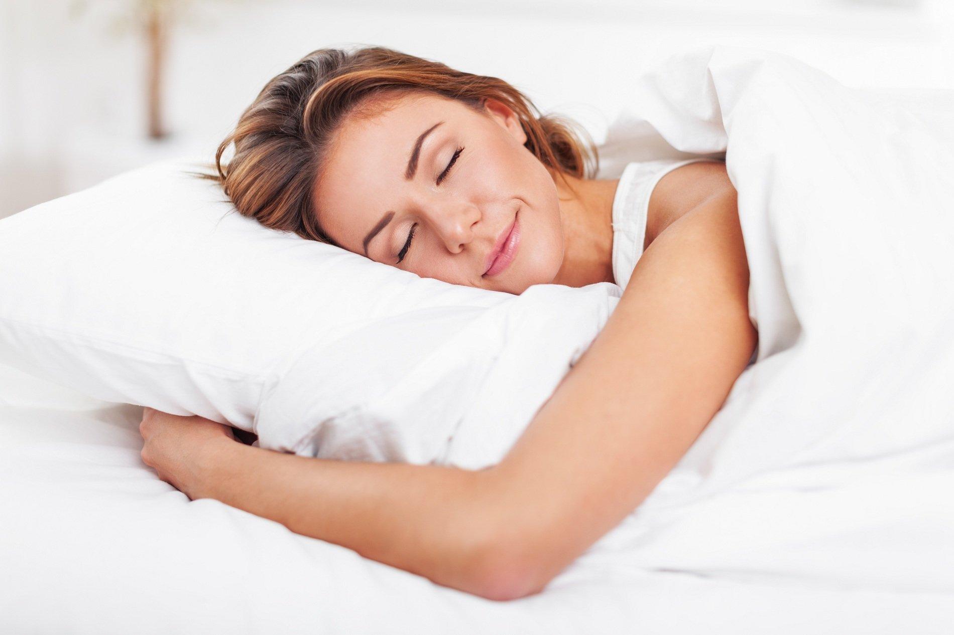 Giovane dormendo con un sorriso e abbracciando il cuscino