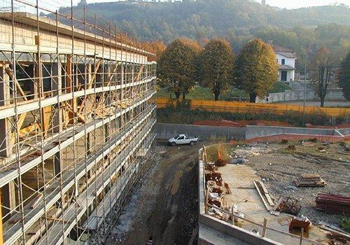 un ponteggio  di un edificio in costruzione e  un pick up bianco