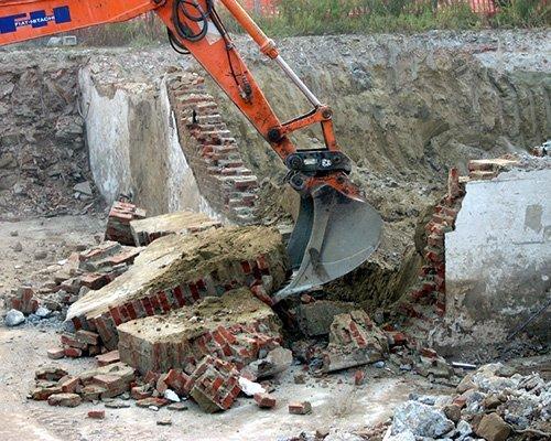 una scavatrice che solleva delle macerie
