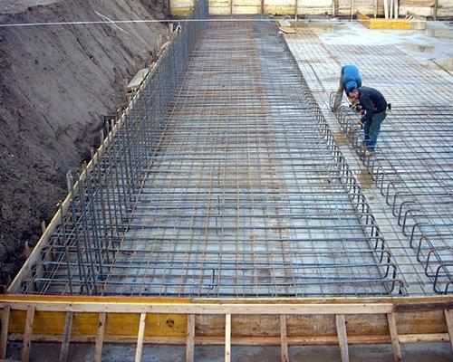 due uomini al lavoro con delle reti metalliche in un edificio in fase di costruzione