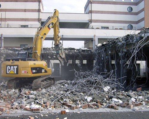 una ruspa demolitrice e delle macerie