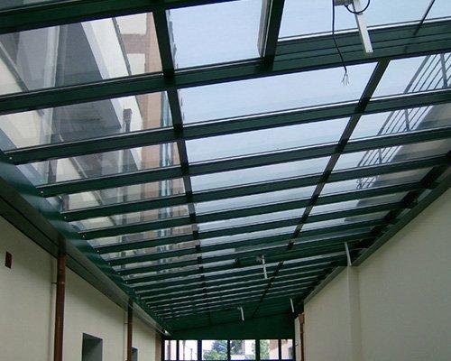 una tettoia in vetro con travi verdi