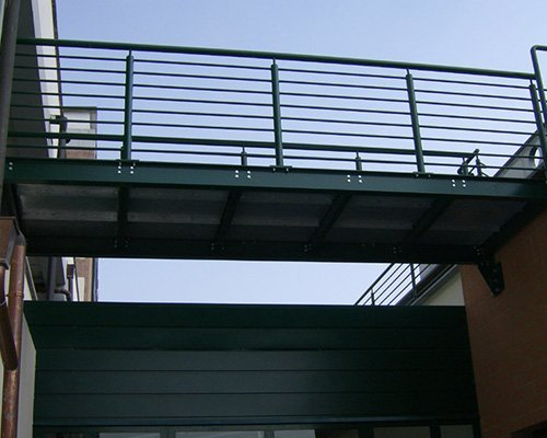 una passerella con corrimano e parapetto che congiunge due edifici