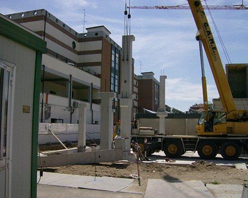 Gru sollevando i pilastri di cemento