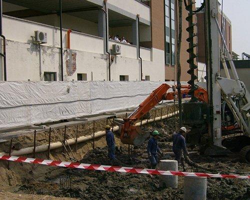 dei muratori in un cantiere e dei mezzi da lavoro