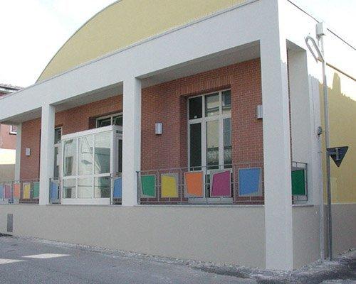 un edificio con  un piccolo portico e dei parapetti a colori