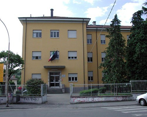 un edificio giallo con fuori la bandiera dell'Italia e dell'Europa