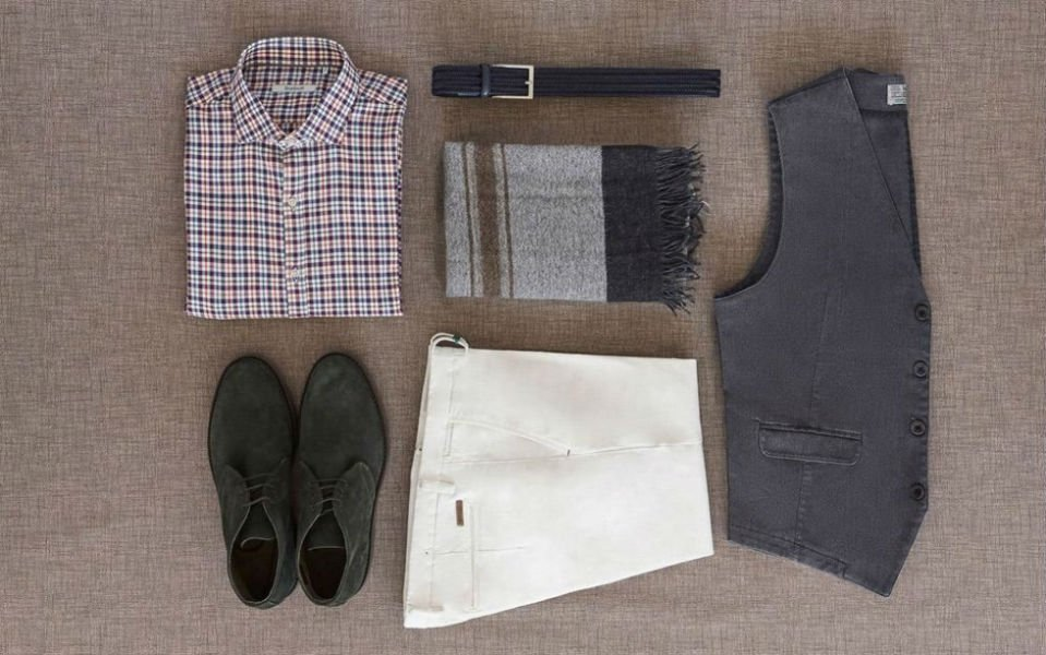 una camicia a scacchi, pantaloni bianchi, un gilet grigio e delle scarpe in camoscio