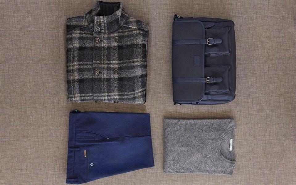 un paio di pantaloni blu, maglietta grigia , una giacca scozzese e una borsetta di color blu