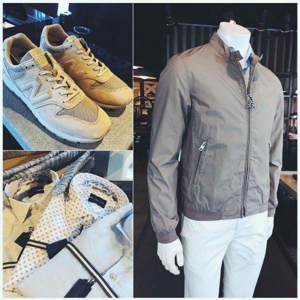 un manichino con un paio di pantaloni di color bianco, una giacca grigia e accanto delle scarpe di New Balance