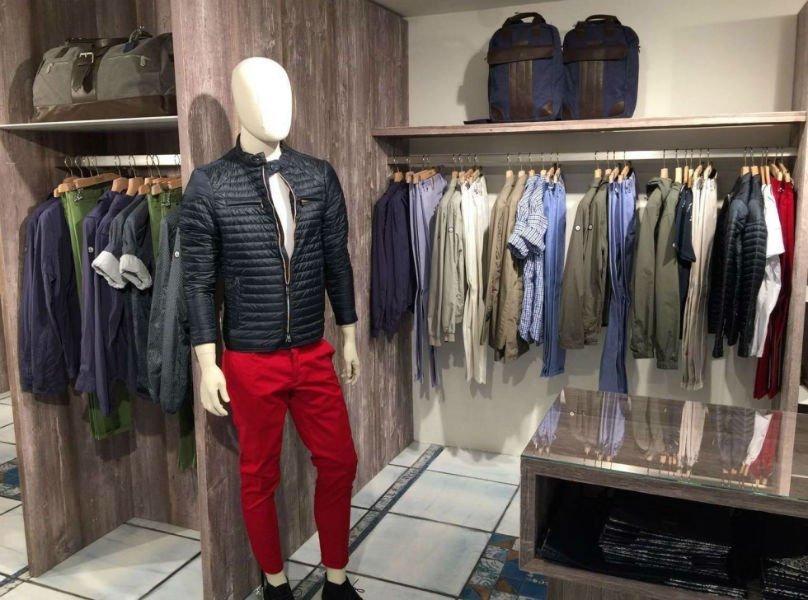 un manichino con un paio di pantaloni rossi, un piumino e accanto deglii appendini con camicie e pantaloni da uomo