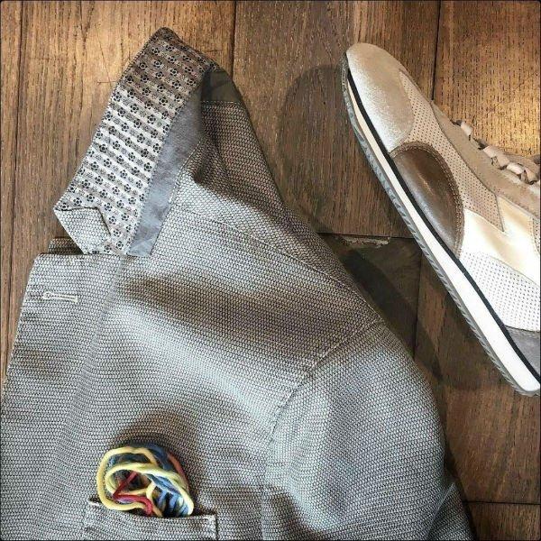 una giacca di color grigio e accanto una scarpa beige