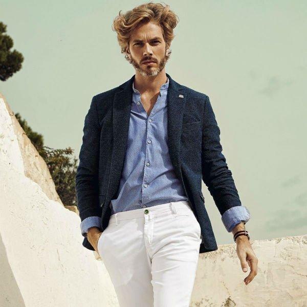 un uomo con dei pantaloni bianchi, camicia azzurra e una giacca blu