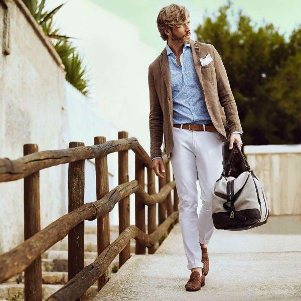 un uomo con pantaloni bianchi, camicia azzurra e una giacca marrone