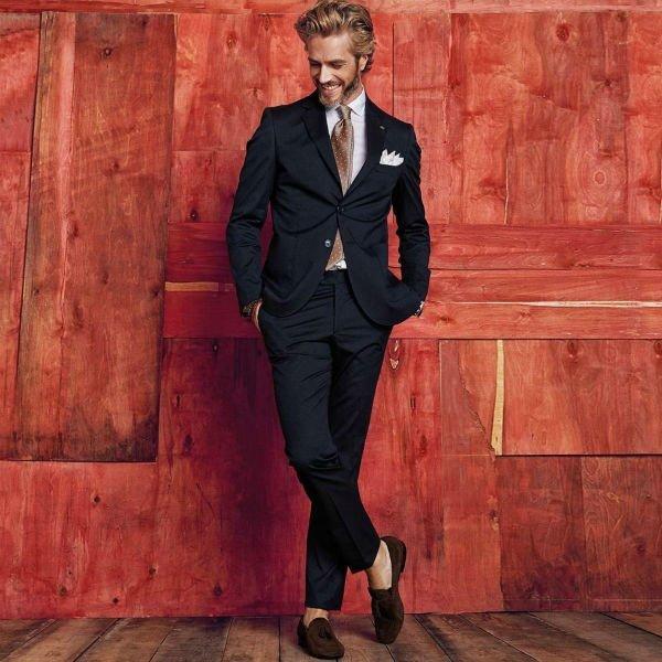 un uomo con una camicia , cravatta marrone e un completo nero