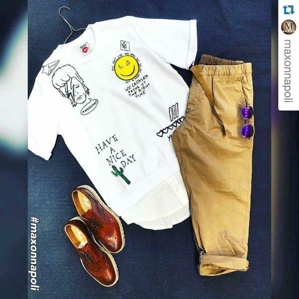 una maglietta bianca, pantaloni beige e delle scarpe di pelle di color marrone