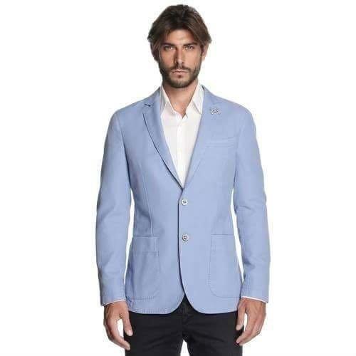 un uomo con una camicia bianca, pantaloni neri e una giacca azzurra