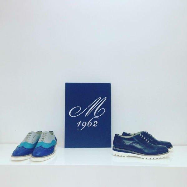 due paia di scarpe di pelle di color blu e grigio