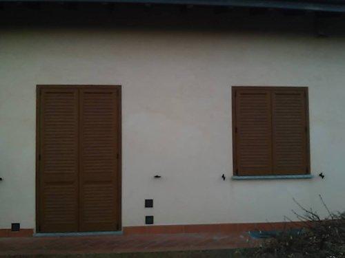 ingresso della casa con porta e finestra in persiane