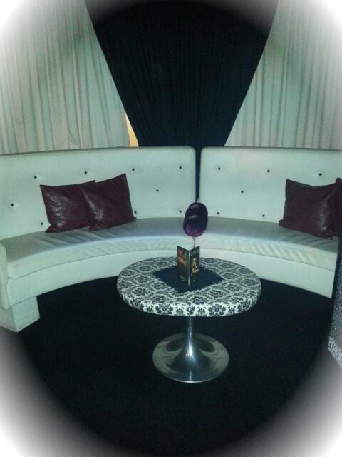 Vista di un sofà semicircular bianco con cuscini neri e piccola tavola per le coppe