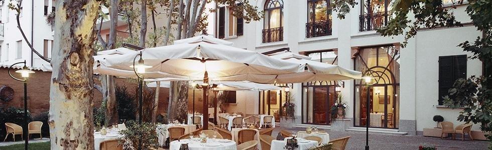 Ristorante estero dell'hotel con mobili di vimini e ombrelloni quadrate