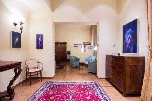 Corridoio dell'hotel, tabelle in tonalità blu e mobili antichi di legno