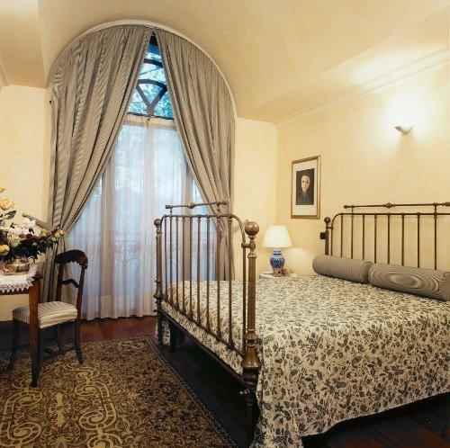 Camera da letto con letto di ottone ,tende beige e mobili di legno vecchi