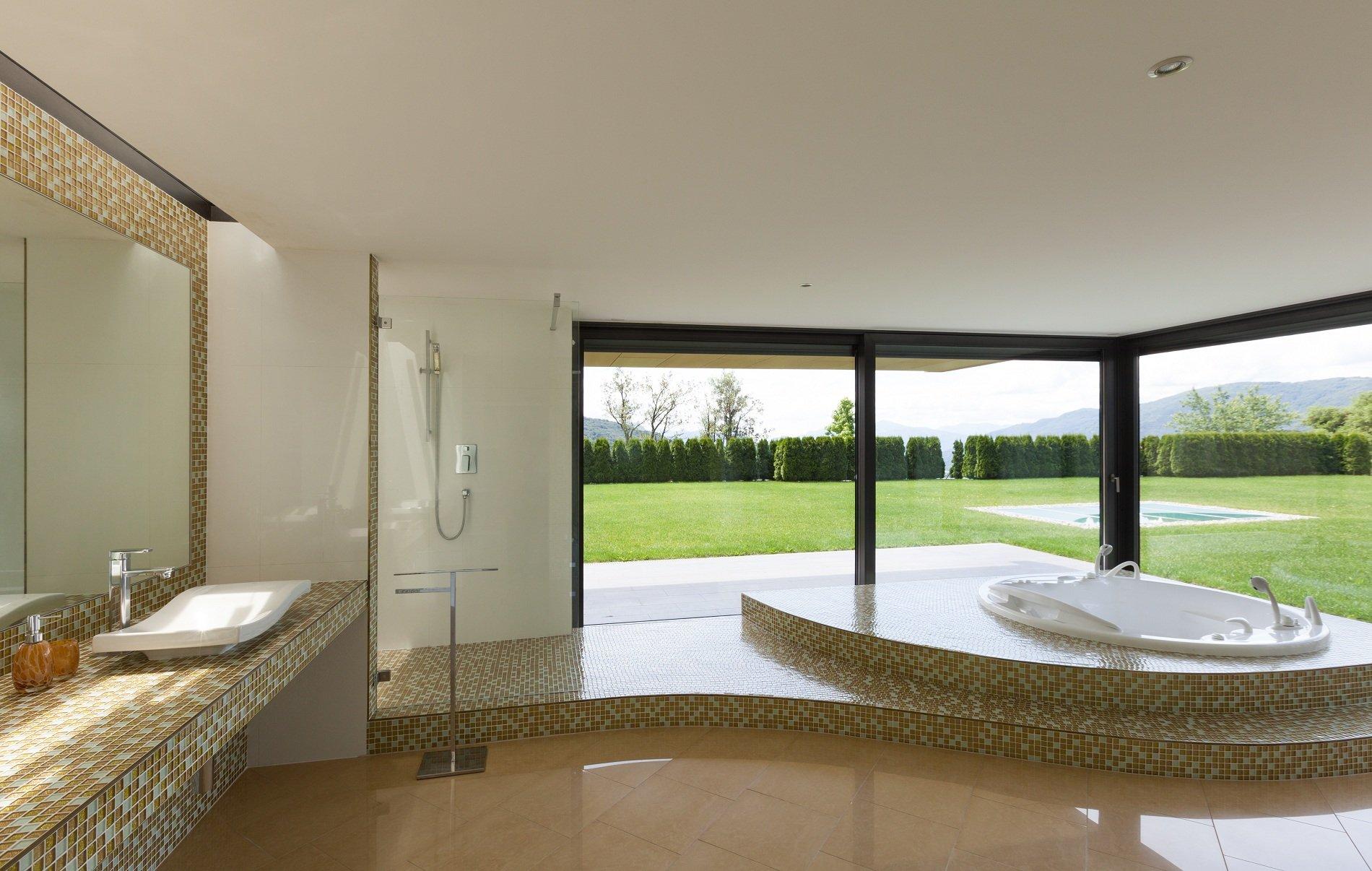 Bagno con pavimento in marmo e pareti,lavabo,zona doccia e vasca con rivestimento in piastrelle di porcellana di colore marrone e bianco